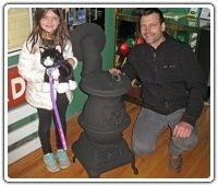 Martin Merva and his daughter Piper are seen with the restored B&M #1 potbelly stove that they donated to the Friends.